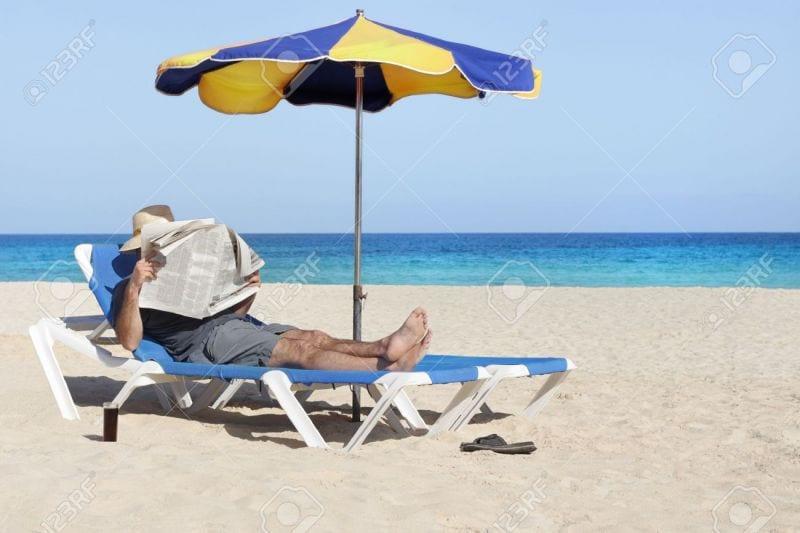 20018045-Lazy-relaxing-newspaper-reading-man-at-beach-Stock-Photo-umbrella