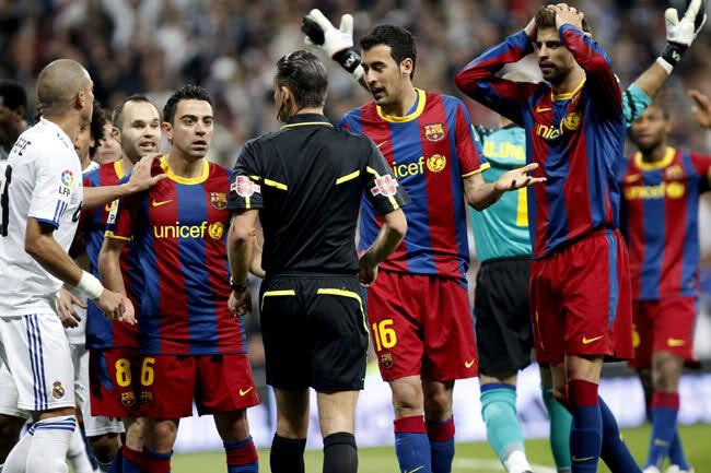 Jugadores del Barcelona rodean al árbitro.